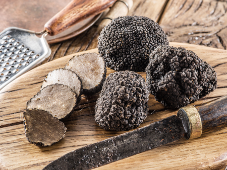 Black truffles on the old wooden table.