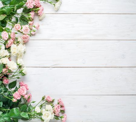 白の木製の背景に繊細な新鮮なバラ。