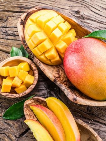 frutas tropicales: Fruta del mango y mango cubos en la mesa de madera. Foto de archivo