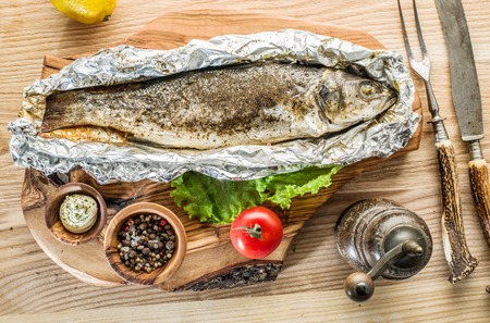 Grilled sea bass fish on the wooden tray.