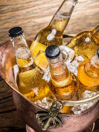seau d eau: bouteilles de bière fraîche dans le seau d'airain sur la table en bois. Banque d'images