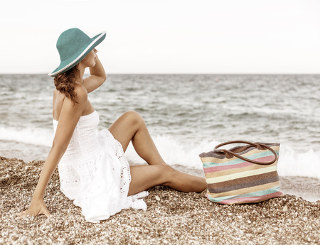 woman bag: Woman relaxing at the seaside. Vintage style. Stock Photo