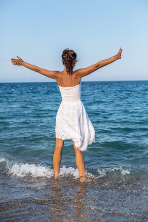 stays: Happy woman stays in the sea water. Stock Photo