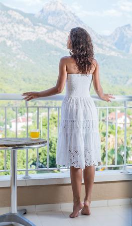silencio: La mujer está en el balcón del hotel. verde de la naturaleza en el fondo.