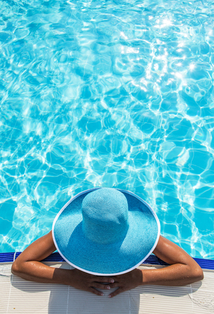 Woman in sun hat in the swimming pool. Top view.