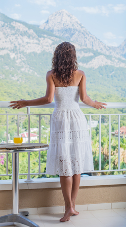 escapism: Woman is on the hotel balcony. Green nature on the background.