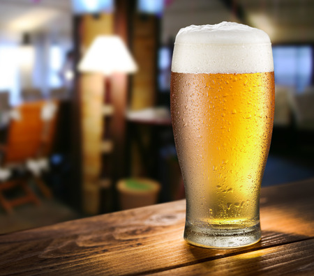 vasos de cerveza: Vaso de cerveza ligera en la barra de vidrio.