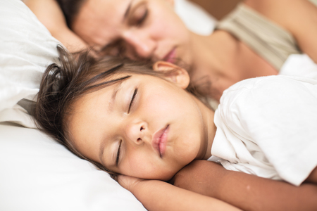 sleeping kid: Sleeping kid girl and her mother in the bed. Stock Photo