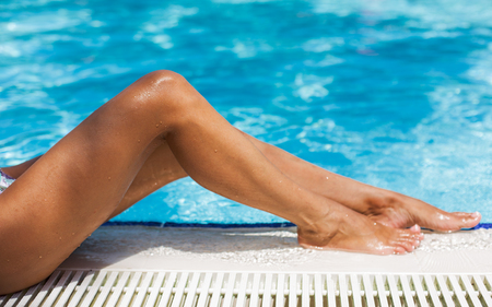tanning: Wet tanned woman legs on the edge of swimming pool. Stock Photo