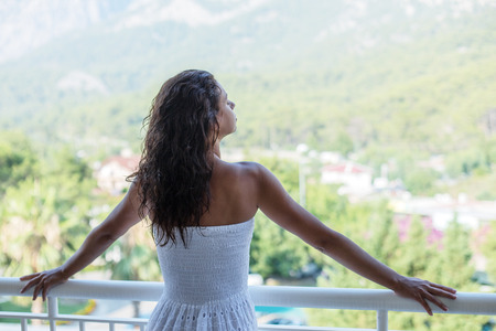 Woman is on the hotel balcony. Green nature on the background. photo