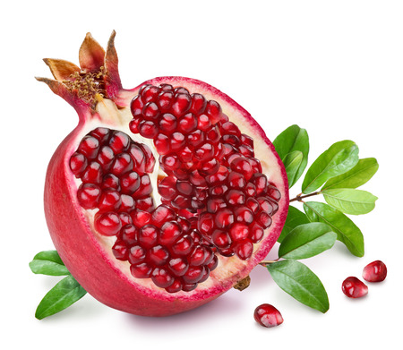 half: Pomegranate fruit with green leaves on the white background. Stock Photo
