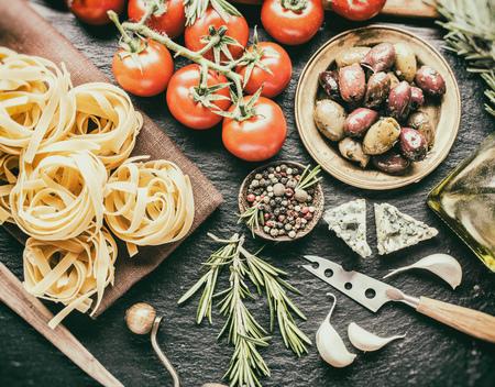 pepe nero: Ingredienti della pasta. Pomodorini, pasta spaghetti, rosmarino e spezie su una scheda di grafite. Stile vintage.