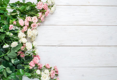 Delicate fresh roses on the white wooden background.