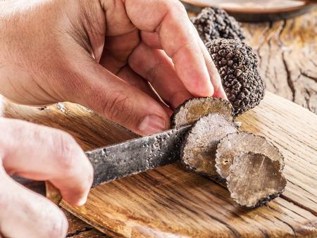 truffle: Cutting of black truffle on the wooden board.