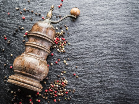 peppercorns: Colorful peppercorns and old pepper mill on the black background.