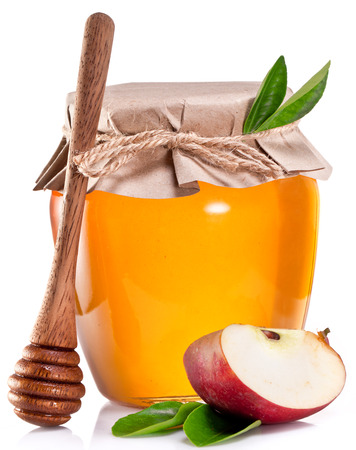 wooden stick: Glass can full of honey, half of apple and wooden stick on old wooden table.