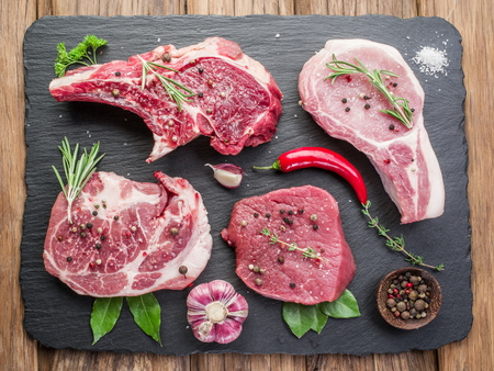 pork: Raw meat steaks with spices on the black cutting board.