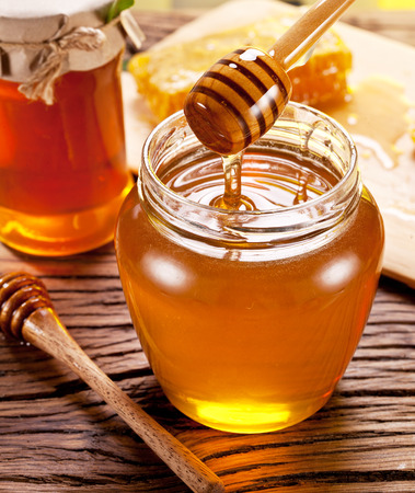 wooden stick: Honey flowing into glass can from wooden stick.