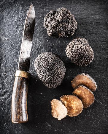 grafit: Black truffles and truffle slices on the graphite board. Zdjęcie Seryjne