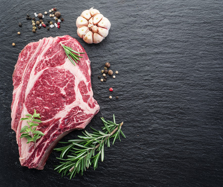 black boards: Rib eye steak with spices on the black background. Stock Photo