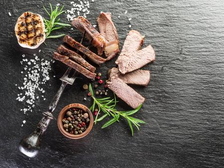 grafito: Chuletón de carne con las especias en la bandeja de grafito. Foto de archivo