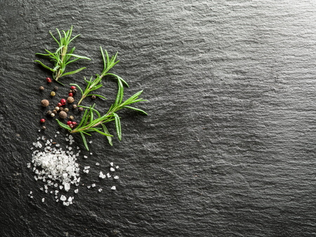 black boards: Salt, rosemary and peppercorns on the graphite board. Stock Photo