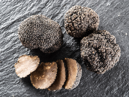 Black truffles and truffle slices on the graphite board. Stock Photo