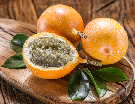 sweet pulp: Granadilla fruits on the wooden table. Stock Photo