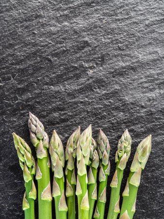 black boards: Green young asparagus sprouts on the black background.