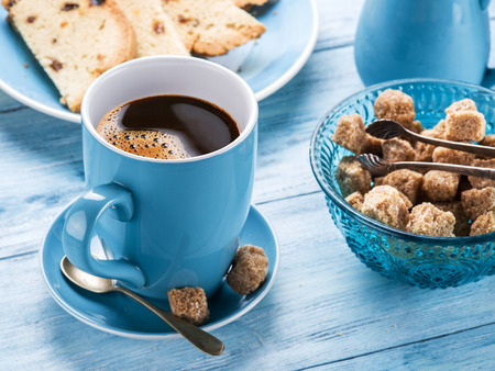 fruitcake: Cup of coffee, milk jug, cane sugar cubes and fruit-cake on old blue wooden table.