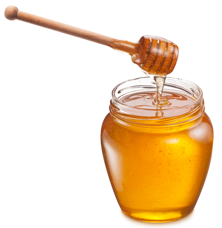 into: Honey flowing into glass jar. File contains clipping paths.