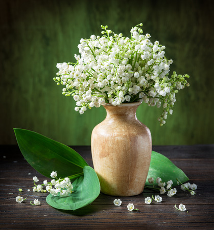 flowers in vase: Lily of the valley bouquet on the wooden table.