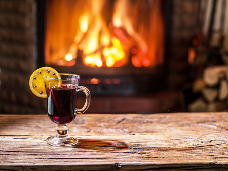 wine background: Hot mulled wine with orange slice, cloves and cinnamon stick. Fireplace with warm fire on the background.