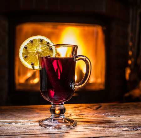 cinnamon stick: Hot mulled wine with orange slice, cloves and cinnamon stick. Fireplace with warm fire on the background.
