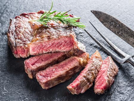 the medium: Medium Ribeye steak with spices on the graphite tray. Stock Photo