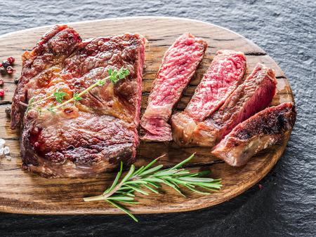 the medium: Medium Ribeye steak with spices on the wooden tray. Stock Photo