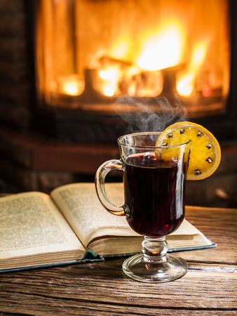 Hot mulled wine and a book on the wooden table. Fireplace with warm fire on the background. Stock Photo