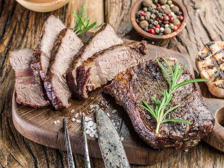 Steak Ribeye with spices on the wooden tray. Stock Photo