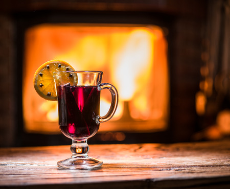glow stick: Hot mulled wine with orange slice, cloves and cinnamon stick. Fireplace with warm fire on the background.
