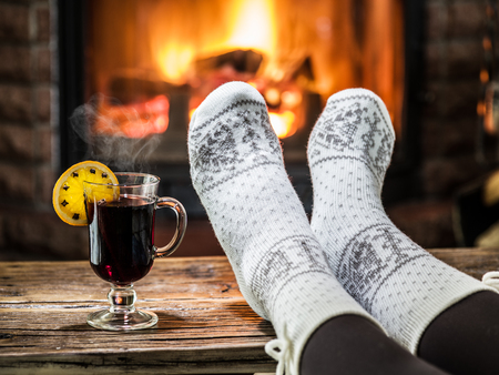 vin chaud: Le r�chauffement et pr�s de chemin�e relaxant. Femme pieds pr�s de la coupe de vin chaud devant le feu. Banque d'images