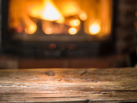 Oude houten tafel en een open haard met een warm vuur op de achtergrond.