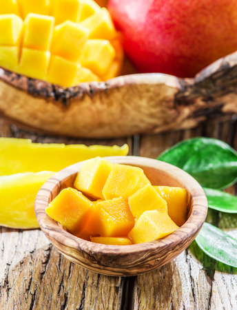 frutas tropicales: Mango fruit and mango cubes on the wooden table.