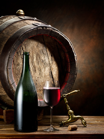 wine testing: Still-life with glass of wine, bottle and barrel on the table in the cellar.