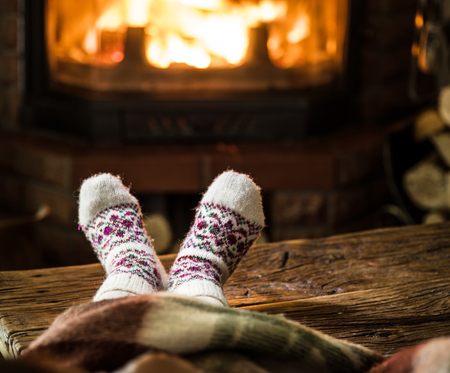 Warming and relaxing near fireplace. Child feet in front of fire. Stock Photo