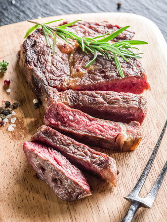 Medium Ribeye steak with spices on the wooden tray. Stock Photo