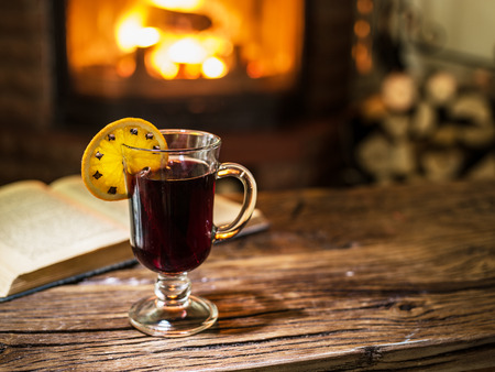 glow stick: Hot mulled wine and a book on the wooden table. Fireplace with warm fire on the background. Stock Photo
