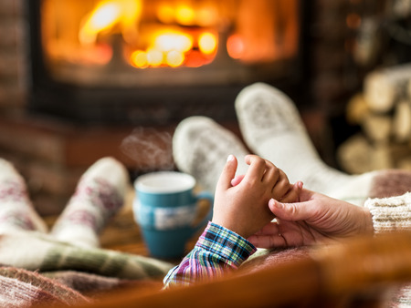Warming and relaxing near fireplace. Mother and daughter holding hands in front of fire. Stock fotó