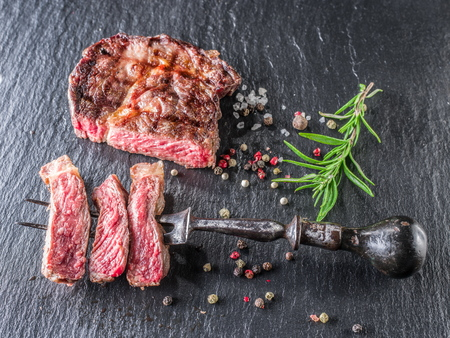 fillets: Medium Ribeye steak with spices on the graphite tray. Stock Photo