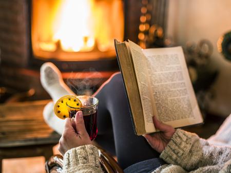 Hete glühwein en boek in handen van de vrouw. Ontspannen in de voorkant van brandend vuur in de koude winter dag.