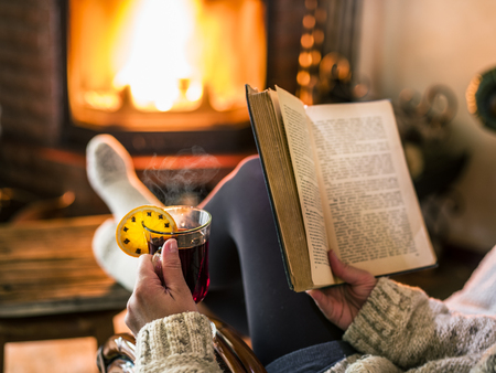 Hot mulled wine and book in woman hands. Relaxing in front of burning fire in the cold winter day. Archivio Fotografico